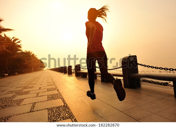 healthy lifestyle fitness woman running at seaside under sunrise