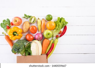 Healthy lifestyle and food concept. Top view paper bag of different fresh vegetables on white wooden background. Flat lay.
