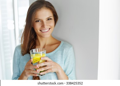 Healthy Lifestyle, Food. Happy Woman Drinking Summer Refreshing Fruit Flavored Infused Water With Fresh Organic Lemon, Lime, Mint. Detox Vitamin-fortified Water. Healthy Eating. Diet Concept.
