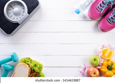 Healthy lifestyle, food and sport concept. Top view of athlete's equipment Weight Scale measuring tape blue dumbbell, sport water bottles, fruit and vegetables on white wooden background.