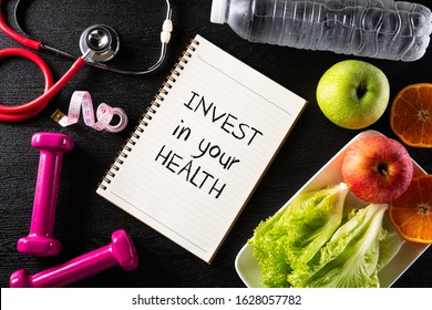 Healthy lifestyle, food and sport concept. Top view of Stethoscope measuring tape pink dumbbell, sport water bottles, fruit and note book with Invest in your health text on black background.