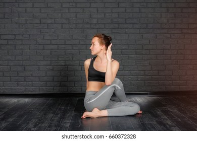 Healthy lifestyle. The girl is practicing meditation in yoga class against a gray brick wall. Relaxation and Stretching. Young slim sporty woman do yoga indoors.