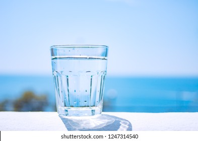 Healthy lifestyle. A glass beaker filled with clear water stands on a sandy beach by the sea.
