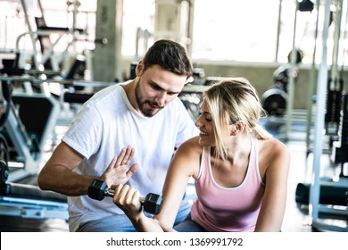 Healthy lifestyle happy couple working out in fitness gym doing weight trainning