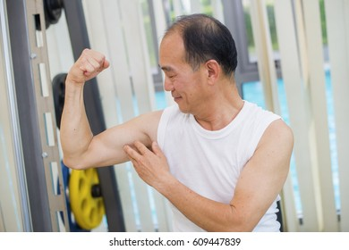 Healthy lifestyle. Happy elderly man showing his muscle strong arms at gym.