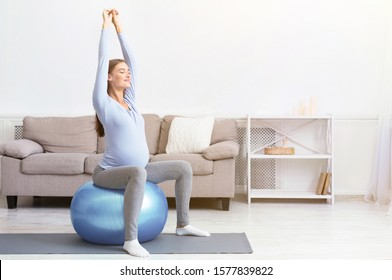 Healthy Lifestyle. Happy pregnant woman exercising on fitball at home. Free space