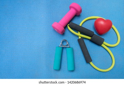 Healthy lifestyle for heart sport dumbbell equipment fitness on blue yoga mat background. Healthy Concept