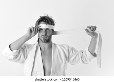Healthy lifestyle and jujitsu concept. Karate fighter with strong body holds white belt. Guy poses in white kimono ties eyes with belt. Man with confident face and bristle isolated on white background