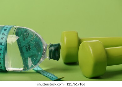Healthy lifestyle and low calorie drink concept. Dumbbells in green color, water bottle and measure tape on green background. Sports regime idea. Bottle tied with cyan ruler by lightweight barbells