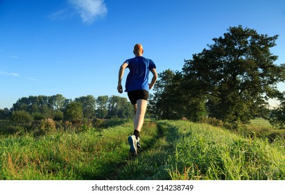 Healthy lifestyle: man running in the countryside on a sunny morning.