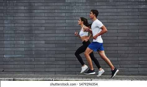 Healthy lifestyle. Man and woman have fitness day and running in the city at daytime near brick wall.