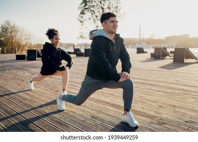 Healthy lifestyle. A man and a woman are stretching along the embankment. Load on the heart cardio system. A couple in love together. Outdoor sports activities. Training in a park in the city center.