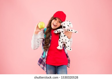 Healthy lifestyle. Mental and physical wellbeing. Schoolgirl daily life. Stylish schoolgirl. Reduce stress. Girl little fashionable schoolgirl with backpack carry soft toy dog and hold apple.