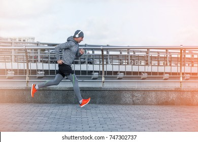 healthy lifestyle middle aged man runner running on city bridge road cold season Motion shot