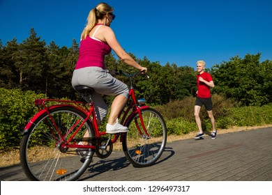 Healthy lifestyle - middle-aged woman riding bike and young man running