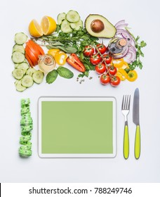 Healthy lifestyle and modern dieting concept.  Various fresh salad vegetables with cutlery and measuring tape around PC tablet . Copy space for shopping list, recipes, dieting plan or menu. Top view