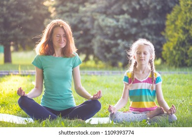 Healthy lifestyle - mom and daughter doing yoga in the park. Healthy and Yoga Concept