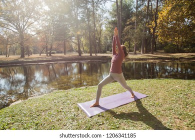Healthy lifestyle in nature,Woman doing yoga exercise on mat in park near lake at beautiful morning autumn day.