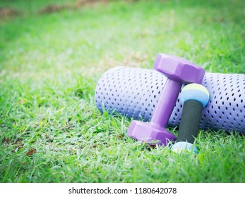 healthy lifestyle and outdoor concept from close up exercise object with shoe dumbbell and yoga mat on grass with copy space and park with lake background