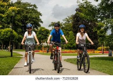 Healthy lifestyle - people riding bicycles in city park