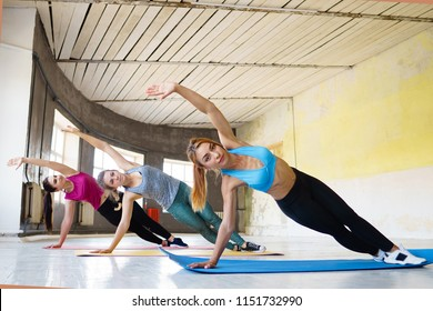 Healthy lifestyle, power, endurance, sport, fitness. Women group workout. Sporty ladies doing static exercise in gym