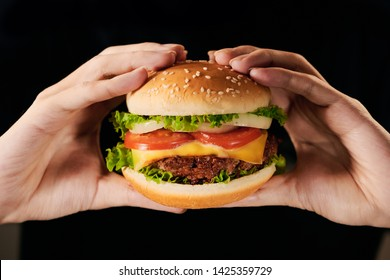Healthy lifestyle, proper nutrition. Healthy rice burger with vegetables, herbs and cutlet in female hands. Horizontal frame