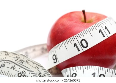 Healthy Lifestyle. Red apple and tape measure on white background. Closeup.