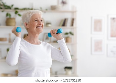 Healthy Lifestyle. Smiling Senior Lady Exercising With Dumbbells At Home, Free Space