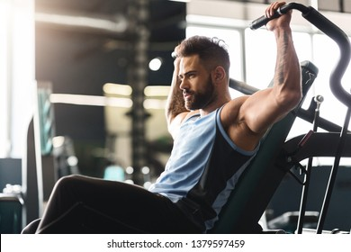 Healthy lifestyle and sport concept. Young man exercising with training apparatus in gym, empty space
