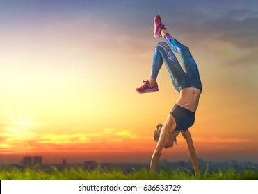 Healthy lifestyle and sport concepts. Woman in fashionable sportswear is doing exercise on nature. Girl on sunset background.