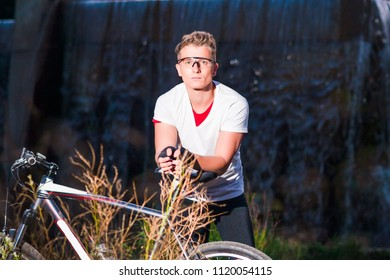 Healthy Lifestyle and Sport Concepts.Caucasian Male Athlete with Mountain Bike Posing Against Waterfall Outdoors. Horizontal image