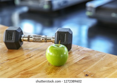 Healthy lifestyle sport. Dumbbells, and healthy food on wooden.  green apple in the gym or sport club. Healthy lifestyle sport equipment fitness