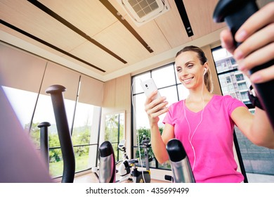 Healthy lifestyle and sport. Pretty young woman exercising in gym using smartphone.