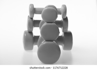 Healthy lifestyle and sports concept. Barbells in different size, close up. Health regime and fitness symbols. Dumbbells made of blue, pink and green plastic on white background, selective focus