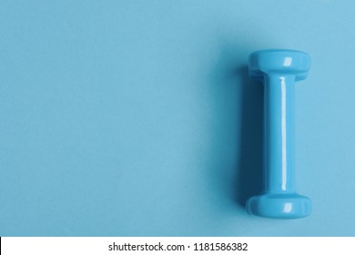 Healthy lifestyle and sports concept. Health regime and fitness symbols. Barbell in small size, top view and copy space. Dumbbell made of blue plastic on blue background
