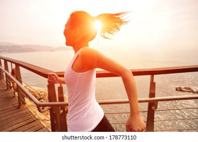 healthy lifestyle sports woman running on wooden boardwalk seaside