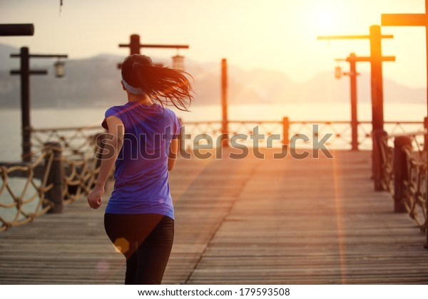 healthy lifestyle sports woman running on wooden pier