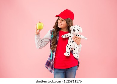 Healthy lifestyle. Stylish schoolgirl. Reduce stress. Girl little fashionable schoolgirl with backpack carry soft toy dog and hold apple. Mental and physical wellbeing. Schoolgirl daily life.