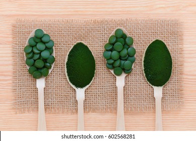 healthy lifestyle, superfood, seaweed, spirulina and chlorella pills and powder on wooden