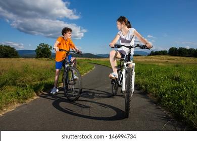 Healthy lifestyle - teenage girl and boy riding bikes