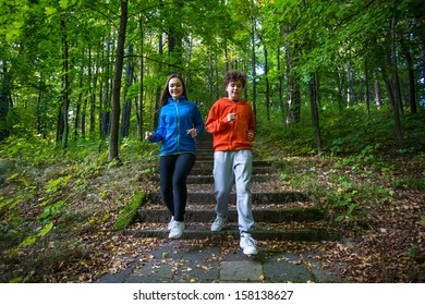 Healthy lifestyle - teenage girl and boy running, jumping outdoor