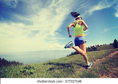 healthy lifestyle woman trail runner running on mountain peak