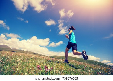 healthy lifestyle woman trail runner running on mountain trail
