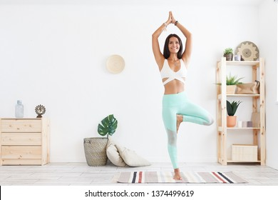 Healthy lifestyle and yoga - a young charming woman a yoga instructor in gymnastic costume makes one of the main asanas - Vrikshasana. Copyspace