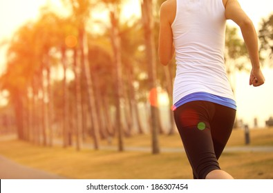 healthy lifestyle young asian sporty woman jogging at tropical park