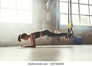 Healthy lifestyle. Young athletic woman doing plank with trx fitness straps in the gym