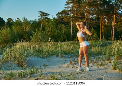 Healthy lifestyle: young fitness girl , out sunset  outdoors doing lunge warming up on the beach with pines