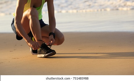healthy lifestyle young fitness woman runner tying shoelace on beach