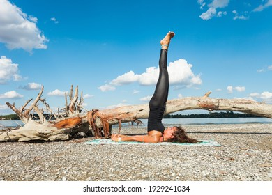 healthy lifestyle young woman practice yoga at river beach at fresh air sunny summer day inverted pose