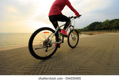 healthy lifestyle young woman ridin bike on seaside